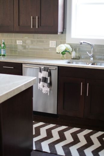 Grey countertop and tile, dark wood cabinets.